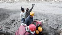 Seorang pria bereaksi setelah dia ditarik keluar dari bawah tanah oleh personel ITBP selama operasi penyelamatan setelah sebagian gletser Nanda Devi terputus di daerah Tapovan, negara bagian utara Uttarakhand, India (7/2/2021). (Indo Tibetan Border Police via AP)