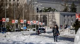 Seorang wanita berjalan di sepanjang Paseo Castellana yang tertutup salju di Madrid, Senin (11/1/2021). Ibu kota Spanyol itu berusaha bangkit kembali setelah menghadapi badai salju terburuk dalam 50 tahun terakhir yang melumpuhkan sebagian besar wilayah Spanyol tengah. (AP Photo/Manu Fernandez)