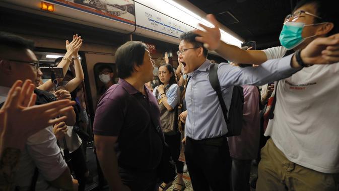 Penumpang berdebat dengan pengunjuk rasa yang mengganggu jalur kereta bawah tanah di Hong Kong (30/7/2019). Pengunjuk rasa telah mengganggu layanan kereta bawah tanah pada pagi hari perjalanan dengan menghalangi pintu-pintu masuk kereta dan mencegah mereka meninggalkan stasiun. (AP Photo/Vincent Yu)