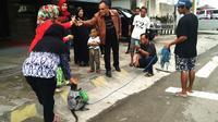Pertunjukan topeng monyet yang menyapa warga depan Terminal Kota Palopo, Sulawesi Selatan. (Liputan6.com/Ahmad Yusran)