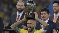 Kapten Timnas Brasil, Dani Alves, mengangkat trofi Copa America 2019 di Stadion Maracana, Rio de Janeiro, Brasil, (AFP/Carl De Souza)