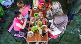 Pengunjung menikmati makan siang sambil digigit ikan dikakinya di restoran kolam ikan di desa Wedomartani di Yogyakarta (15/11/2019). Restoran unik ini dikenal dengan nama Soto Cokro Kembang. (AFP Photo/Oka Hamied)