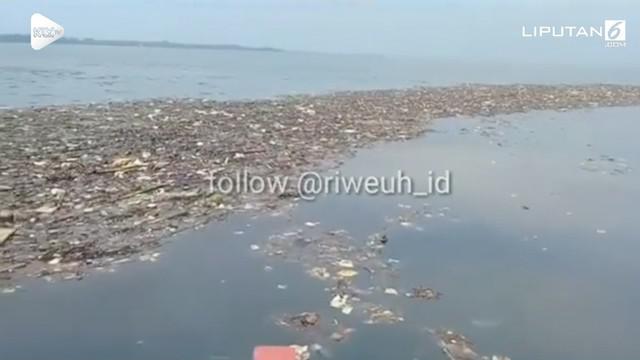 Seorang warga merekam keadaan lautan di sekitar Pulau Pari, Kepulauan Seribu yang penuh sampah berbau busuk dan tercampur limbah aspal.
