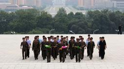 Tentara membawa bunga saat akan memberi penghormatan kepada patung pemimpin Korea Utara Kim Il Sung dan Kim Jong Il dalam peringatan berakhirnya Perang Dunia II dan pembebasan dari kolonial Jepang di Pyongyang, Korut, Rabu (15/8). (AP Photo/Ng Han Guan)