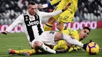 Pemain Juventus Federico Bernardeschi dan pemain Chievo Sofian Kiyine berebut bola pada laga pekan ke-20 Serie A di Allianz Stadium, Senin (21/1). Juventus berhasil memantapkan posisi di puncak klasemen setelah menggilas Chievo 3-0. (Marco BERTORELLO/AFP)