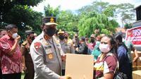 Seorang warga lansia menerima paket sembako gratis saat mengikuti vaksinasi yang digelar oleh Polda Sulut.