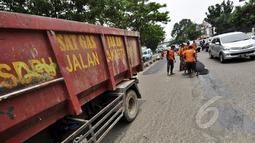 Sejumlah petugas mengaspal jalanan yang berlubang di Jalan Kramat Raya, Jakarta, Rabu (25/2/2015). Pascabanjir beberapa waktu lalu, sebanyak 700 titik lubang bermunculan di jalan Ibukota. (Liputan6.com/Faizal Fanani)
