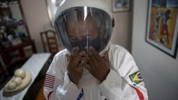 Akuntan Brasil Tercio Galdino (66) mengenakan helm saat akan pergi ke Pantai Copacabana dengan pakaian pelindung mirip astronaut di Rio de Janeiro, Brasil, 12 Juli 2020. Pakaian tersebut juga dipakai untuk bersenang-senang karena minatnya yang besar dalam astronomi. (Mauro Pimentel/AFP)