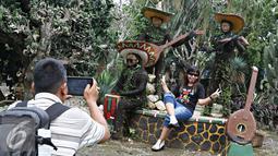 Pengunjung berfoto di sekitar Taman Meksiko, Kebun Raya Bogor, Jawa Barat, Senin (28/3). Di taman tersebut, terdapat 100 jenis kaktus, agave, yucca, dan sukulen yang berasal dari gurun Amerika serta Asia. (Liputan6.com/Immanuel Antonius)