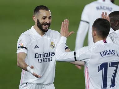 Striker Real Madrid, Karim Benzema (kiri) merayakan gol pertama Real Madrid yang dicetaknya ke gawang Barcelona dalam laga lanjutan Liga Spanyol 2020/2021 pekan ke-30 di Alfredo di Stefano Stadium, Madrid, Sabtu (10/4/2021). Real Madrid menang 2-1 atas Barcelona. (AP/Manu Fernandez)