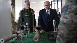 Presiden Rusia, Vladimir Putin bersama Menteri Pertahanan Rusia Sergei Shoigu  mengunjungi pameran Kalashnikov Concern di Patriot Park, luar Moskow, Rabu (19/9). (Alexey NIKOLSKY / SPUTNIK / AFP)