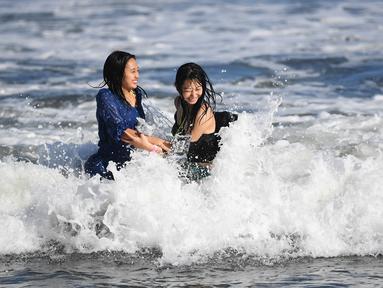 Dua wanita menikmati ombak di sepanjang pantai dekat Pulau Enoshima di pantai Prefektur Kanagawa, barat daya Tokyo (13/8/2019). Enoshima adalah pulau lepas pantai kecil, sekitar 4 km di sekelilingnya, di mulut Sungai Katase yang mengalir ke Teluk Sagami di Prefektur Kanagawa, Jepang. (AFP Photo/Char
