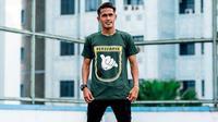 M. Sidik Saimima, memamerkan kaos jualannya yang berbau Persebaya. (Bola.com/Zaidan Nazarul)