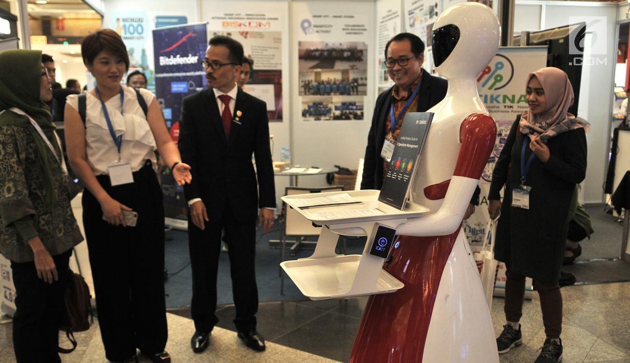 Pengunjung saat melihat aksi robot pintar yang dipamerkan salah satu stan Indonesia International Smart City di JCC Senayan, Jakarta, Rabu (17/7/2019). Pameran ini digelar oleh PT Napindo Media Ashatama bekerjasama dengan sejumlah kementerian dan instansi terkait. (merdeka.com/Iqbal S. Nugroho)