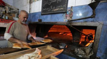 Seorang tukang roti Irak menyiapkan roti isi selama bulan suci Ramadan di toko rotinya di sebuah pasar populer di Baghdad (24/5/2019). Baghdad adalah kota terbesar kedua di Asia Barat Daya setelah Teheran, dengan populasinya pada 2003 diperkirakan mencapai 5.772.000. (AFP Photo/Ahmad Al-Rubaye)