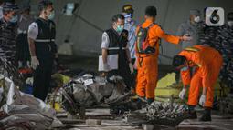 Petugas Basarnas mengumpulkan puing pesawat Sriwijaya Air nomor penerbangan SJ 182 rute Jakarta-Pontianak pada hari ketujuh operasi SAR pesawat tersebut di JICT II Tanjung Priok, Jakarta Utara, Jumat (15/1/2021). (Liputan6.com/Faizal Fanani)