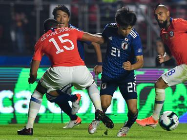 Gelandang Jepang, Takefusa Kubo (tengah) berusaha melewati dua pemain Chile, Jean Beausejour dan Arturo Vidal selama pertandingan grup C Copa America 2019 di Stadion Morumbi, Sao Paulo, Brasil (17/6/2019). Kubo merupakan remaja 18 tahun yang dijuluki 'Messi Jepang'. (AFP Photo/Nelson Almeida)
