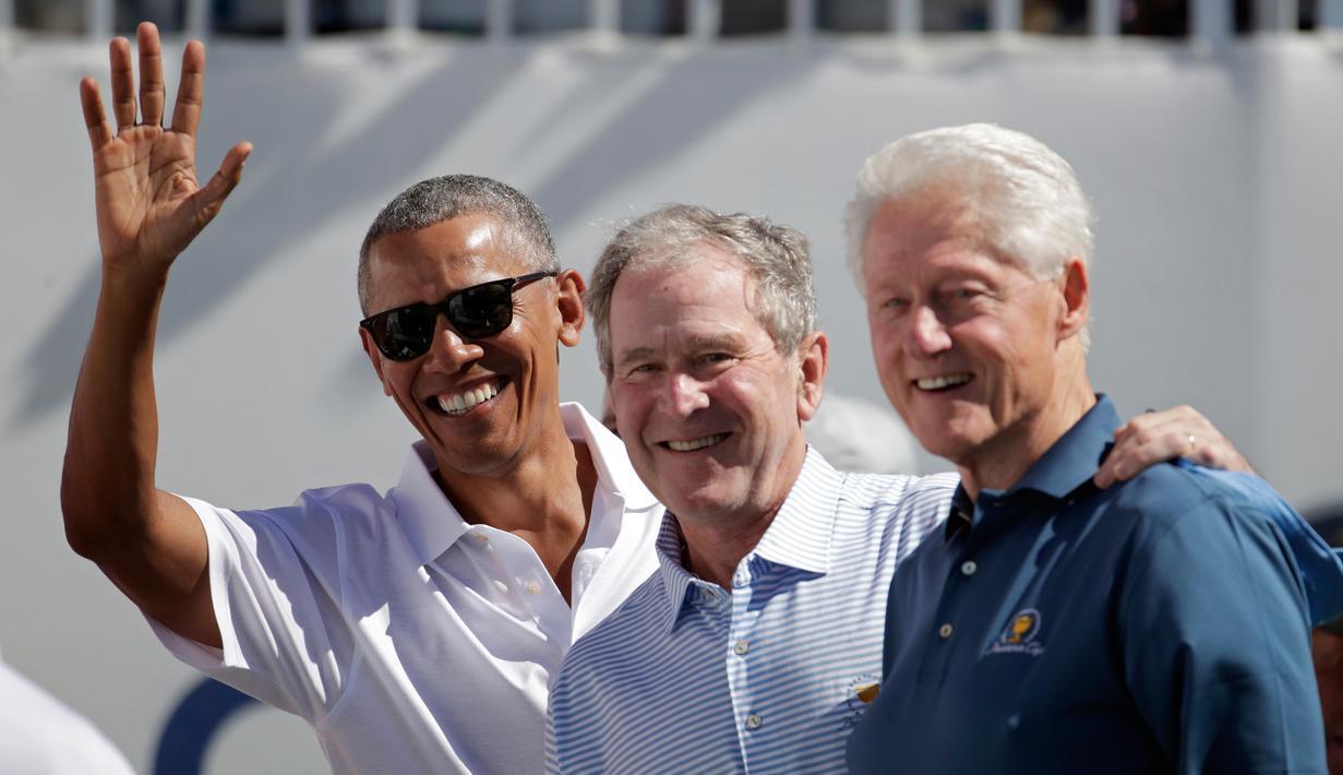Mantan Presiden AS, Barack Obama, George W Bush dan Bill Clinton menyapa penonton saat upacara pembukaan pertandingan golf President Cup di New Jersey, Kamis (28/9). Ini pertama kalinya tiga presiden datang bersama di turnamen tersebut. (AP/Julio Cortez)