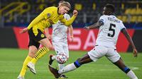 Penyerang Borussia Dortmund, Erling Braut Haaland, berebut bola dengan bek Club Brugge, Odilon Kossounou, pada laga lanjutan Liga Champions di Signal Iduna Park, Rabu (25/11/2020) dini hari WIB. Borussia Dortmund menang 3-0 atas Club Brugge. (AFP/Ina Fassbender)