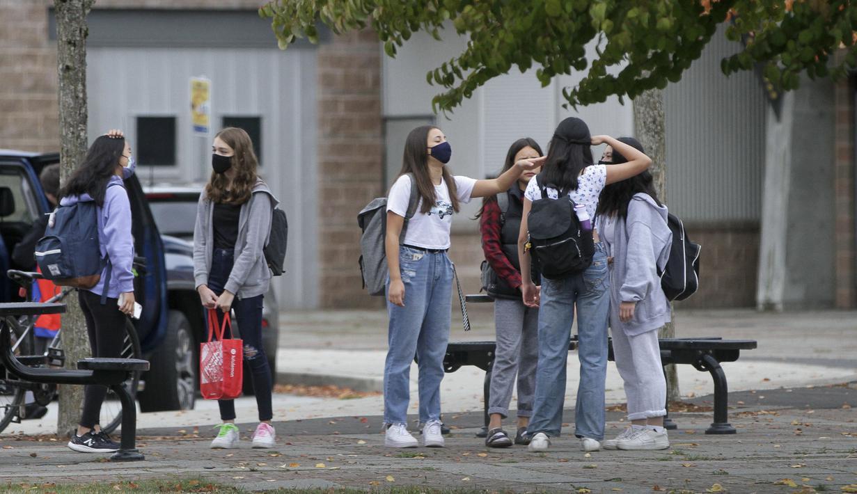 Para siswa yang mengenakan masker terlihat di sebuah sekolah di Vancouver, British Columbia, Kanada, 21 September 2020. Paparan COVID-19 telah dilaporkan di sedikitnya 20 sekolah di British Columbia sejak para siswa kembali belajar di sekolah dua pekan lalu. (Xinhua/Liang Sen)