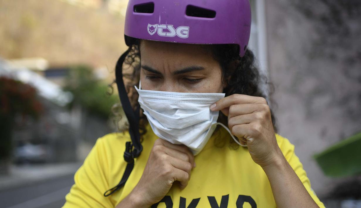 Atlet BMX asal Venezuela, Stefany Hernandez mengenakan masker sebelum latihan di Caracas, 25 April 2020. Di tengah karantina wilayah guna mengekang penyebaran Covid-19, peraih medali Olimpiade 2016 itu berlatih tiga kali seminggu untuk meraih tiket tampil di Olimpiade 2021. (AP/Matias Delacroix)