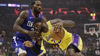 LeBron James (kuning) berduel dengan Kawhi Leonard pada laga hari pertama NBA 2019-2020 (AP)