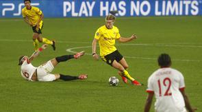 Striker Borussia Dortmund, Erling Haaland, melewati pemain Sevilla, Nemanja Gudelj, pada laga Liga Champions di Stadion Ramon Sanchez Pizjuan, Kamis (18/2/2021). Dortmund menang dengan skor 2-3. (AP/Angel Fernandez)