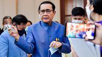 PM Thailand, Prayut Chan-O-Cha menyemprotkan pembersih tangan ke wartawan untuk menghindari pertanyaan perombakan kabinet selama konferensi pers di Bangkok, Selasa (9/3/2021). Sebelum menyemprot, Prayuth mengatakan kepada wartawan untuk mengurus urusan mereka sendiri. (HO/ROYAL THAI GOVERNMENT/AFP)