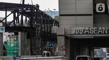 Pekerja menyelesaikan jembatan layang integrasi antara Stasiun MRT ASEAN dengan Halte Transjakarta CSW koridor 13, Jakarta, Rabu (8/1/2020). Jembatan layang ini nantinya akan memudahkan penumpang untuk mengakses salah satu moda transportasi baik MRT atau Transjakarta. (Liputan6.com/Faizal Fanani)