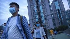 Orang-orang yang memakai masker untuk melindungi diri dari COVID-19 berjalan melintasi jembatan penyeberangan di dekat lingkungan dengan dugaan kasus virus corona di Beijing, Rabu (15/9/2021).. (AP Photo/Mark Schiefelbein)