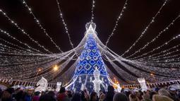 Orang-orang berjalan di dekat pohon Natal raksasa yang menerangi Alun-Alun Katedral di Vilnius, Lithuania, Minggu (1/12/2019). Secara tradisi, pohon Natal Vilnius biasanya berupa rangka logam yang ditutupi dengan dekorasi dan cabang-cabang pohon dari hutan. (AP/Mindaugas Kulbis)