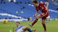 Penyerang Liverpool, Diogo Jota, melepaskan tembakan di tengah pengawalan dari Lewis Dunk, dalam laga pekan ke-10 Premier League 2020-2021 di  American Express Community Stadium, Sabtu (28/11/2020). (AFP/Kirsty Wigglesworth)