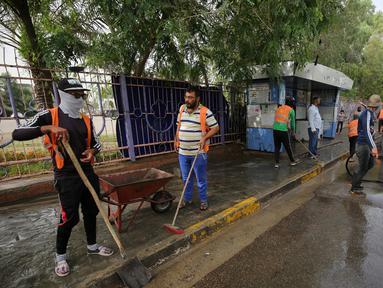 Pekerja kota Irak membersihkan tempat serangan bom bunuh diri semalam di pinggiran Syiah Baghdad di al-Shoala (24/5). Empat orang tewas dan beberapa lainnya terluka ketika seorang pembom bunuh diri menyerang kafe di Baghdad. (AFP Photo/Ahmad Al-Rubaye)