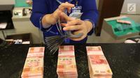 Petugas tengah menghitung uang rupiah di Bank BUMN, Jakarta, Selasa (17/4). Mengacu data Bloomberg, rupiah siang ini pukul 12.00 WIB di pasar spot exchange sebesar Rp 13.775 per dolar AS atau menguat 4,7 poin. (Liputan6.com/Angga Yuniar)