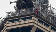 Petugas pemadam kebakaran berusaha mendekati seorang pria yang memanjat Menara Eiffel tanpa peralatan keselamatan di Paris, Senin (20/5/2019). Pasukan pemadam kebakaran harus turun dari lantai tiga dek observasi Menara Eiffel untuk mencapai pria itu. (FRANCOIS GUILLOT / AFP)