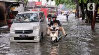 Kendaraan menerobos banjir yang menggenangi Jalan KH. Ahmad Dahlan Cipondoh, Tangerang, Selasa (16/2/2021). Hujan deras yang melanda wilayah Tangerang mengakibatkan ruas jalan alternatif penghubung Tangerang dengan Jakarta tersebut banjir setinggi lutut orang dewasa. (Liputan6.com/Angga Yuniar)