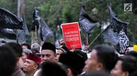 Peserta aksi membawa poster saat berunjuk rasa di Pintu Barat Monas, Jakarta, Selasa (18/7). Terlihat massa memadati pintu Barat Monas dengan membawa atribut aksi spanduk dan bendera. (Liputan6.com/Faizal Fanani)