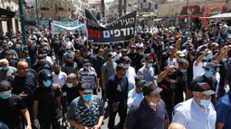 Warga saat menggelar aksi protes di kota pesisir Mediterania, Jaffa, Tel Aviv selatan (26/6/2020). Warga muslim di Israel menggelar aksi protes terhadap keputusan pemerintah Tel Aviv yang akan menggusur situs Tanah Pemakaman Muslim dari abad ke-18. (AFP Photo/Jack Guez)