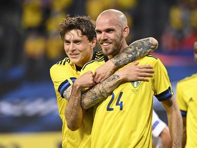 Bek Swedia, Marcus Danielson (tengah) melakukan selebrasi bersama Victor Lindelof usai mencetak gol kedua timnya ke gawang Armenia dalam laga uji coba menjelang berlangsungnya Euro 2020 di Solna, Sabtu (5/6/2021). Swedia menang 3-1 atas Armenia. (AFP/Jonathan Nackstrand)