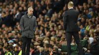 Pelatih Manchester United, Jose Mourinho berbincang dengan samping Josep Guardiola selama pertandingan lanjutan Liga Inggris di stadion Etihad, Inggris, (27/4). MU berada di peringkat ke lima dan City di peringkat empat. (AFP Photo/Oli Scarff)