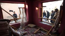 Penduduk desa berdiri di dekat sebuah rumah yang hancur setelah serangan di Kabul, Afghanistan (15/1). Empat orang tewas dan 113 orang lainnya terluka akibat ledakan yang terjadi di dekat kompleks asing tersebut. (AP Photo/Rahmat Gul)