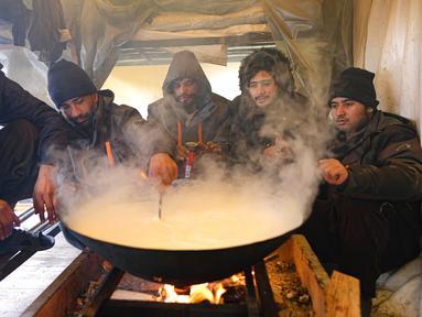 Para imigran memasak dalam tempat penampungan sementara di Kamp Lipa, luar Bihac, Bosnia, Jumat (8/1/2021). Cuaca bersalju dan musim dingin telah membawa lebih banyak penderitaan bagi ratusan imigran yang terjebak selama berhari-hari di kamp tersebut. (AP Photo/Kemal Softic)