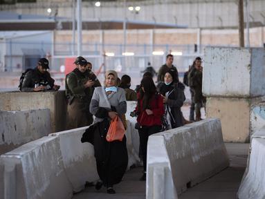 Tentara Israel memeriksa seorang perempuan Palestina saat dia menunggu untuk menyeberangi pos pemeriksaan Qalandia antara kota Ramallah Tepi Barat dan Yerusalem, untuk menghadiri sholat Jumat kedua bulan suci Ramadhan di Masjid Al-Aqsa, Jumat (23/4/2021). (AP Photo/Majdi Mohammed)