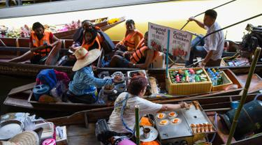 Pedagang menghampiri wisatawan yang sedang naik kapal di pasar terapung Damnoen Saduak, Bangkok, Thailand, Jumat (21/6/2019). Damnoen Saduak menjadi pasar terapung yang wajib Anda datangi saat berwisata ke Negeri Gajah Putih. (TANG CHHIN Sothy/AFP)