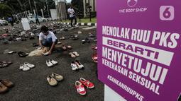 "Pegiat komnas perempuan merapikan sepatu saat aksi diam 500 Langkah Awal Sahkan RUU PKS di depan gedung DPR, Jakarta, Rabu (25/11/2020). Dalam aksinya mereka menyusun sepatu sebagai simbol ""semua peduli, semua terlindungi, stop sexual violence"". (Liputan6.com/Johan Tallo)"