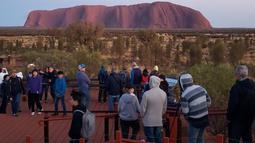 Selebaran yang diterima pada 10 Oktober 2019 memperlihatkan wisatawan memandangi Uluru di Utara Australia.  Pendakian di Batu Ayers tersebut akan dilarang mulai Oktober tahun ini, seiring dengan keinginan Anagu, suku asli Aborigin yang mendiami kawasan tersebut. (HO/ @koki_mel_aus/AFP)