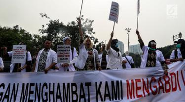 Massa dari Pergerakan Dokter Muda Indonesia melakukan aksi di depan Istana Negara, Jakarta, Kamis (19/7). Mereka ingin mengadukan isu terkait pungli yang dilakukan Fakultas Kedokteran dan Kemenristek Dikti Ke Presiden Jokowi. (Liputan6.com/Johan Tallo)