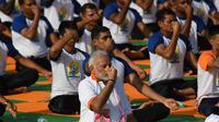 Perdana Menteri India, Narendra Modi memimpin pelaksanaan yoga massal pada Hari Yoga Internasional di Dehradun, Kamis (21/6). Modi adalah tokoh utama yang berhasil melobi PBB untuk menyatakan 21 Juni sebagai Hari Yoga Internasional. (AFP/PRAKASH SINGH)