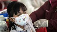 Seorang warga menerima vaksin virus corona COVID-19 Sinovac di pusat vaksinasi massal darurat di lapangan sepak bola di Surabaya, Jawa Timur, Kamis (30/9/2021). Vaksinasi ini dalam rangka percepatan penanganan COVID-19 dan pemulihan ekonomi nasional. (Juni Kriswanto/AFP)