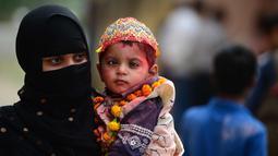 Seorang wanita Muslim India bersama anaknya yang menderita cerebral palsy ambil bagian dalam acara festival Hindu Holi untuk anak-anak dengan cerebral palsy yang diselenggarakan oleh Yayasan Trishla di Allahabad (25/2). (AFP Photo/Sanjay Kanojia)